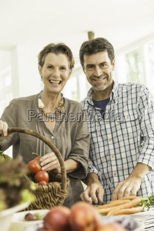 portrait of couple preparing fresh vegetables