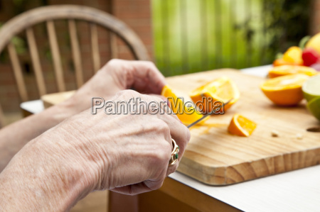 hands of senior woman slicing oranges