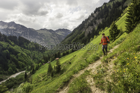 young man hiking on valley path