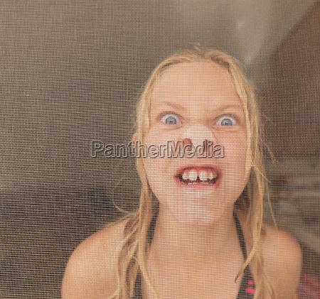 girl pressing nose against screen door