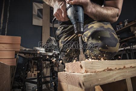 close up of male carpenter drilling