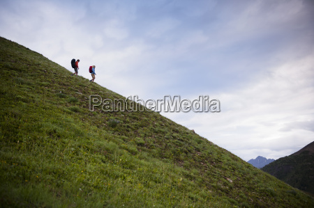 couple hiking on hill near paradise