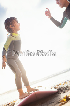 mother and daughter practicing surfing on