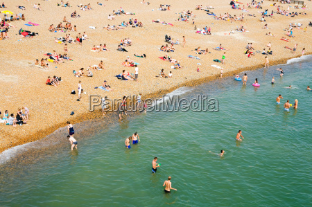 people on crowded beach brighton england