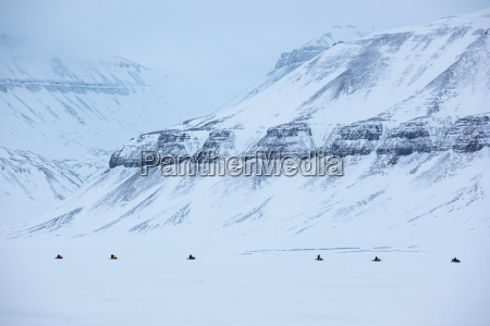 a tour of snowmobiles travel towards
