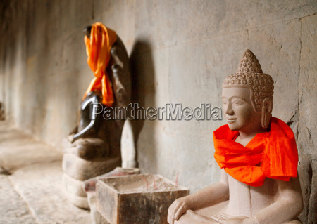 buddhist statues adorned with colourful cloth