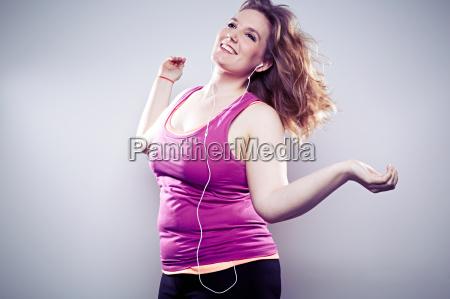 young woman wearing earphones dancing