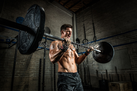 young man performing bicep curls with