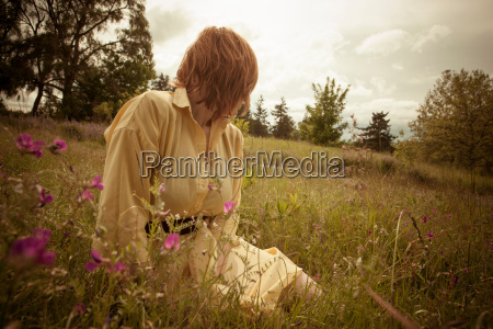 young woman sitting in field looking
