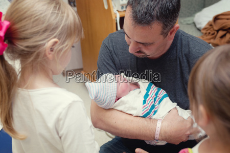 father cradling newborn baby girl with