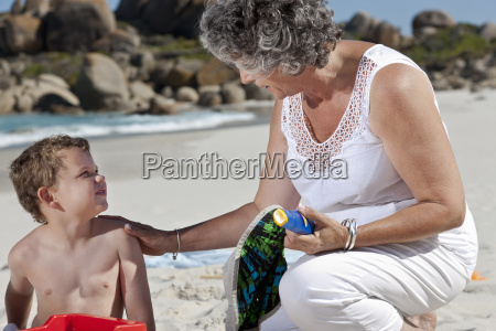 woman sitting with grandson on beach