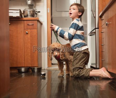 boy holding lead of pet dog