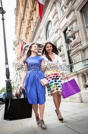 two young women walking down london