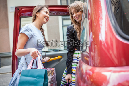 young women getting into taxicab carrying