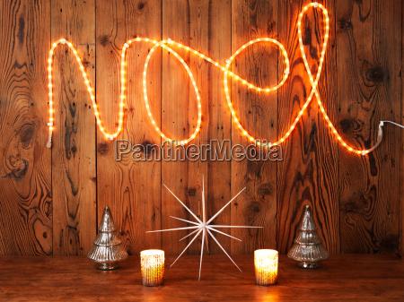 christmas lights spelling noel against wood