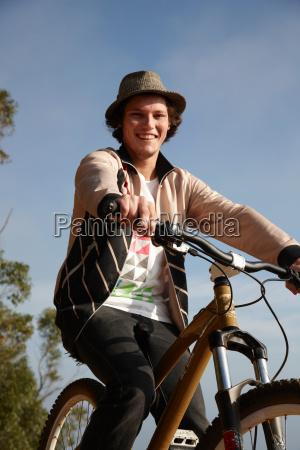 man wearing hat riding mountain bike