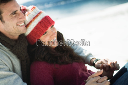 couple in winter sitting back laughing