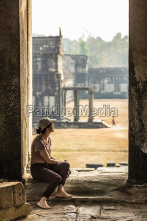 tourist sitting in temple in angkor