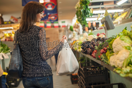woman shopping at greengrocers in market