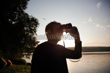 man looking through binoculars at sunset