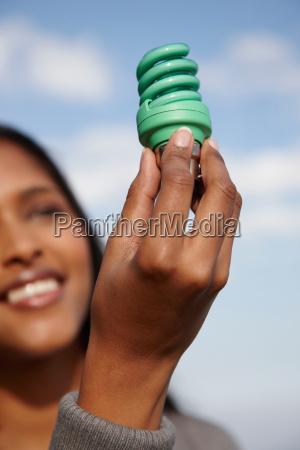 woman holding up green light bulb
