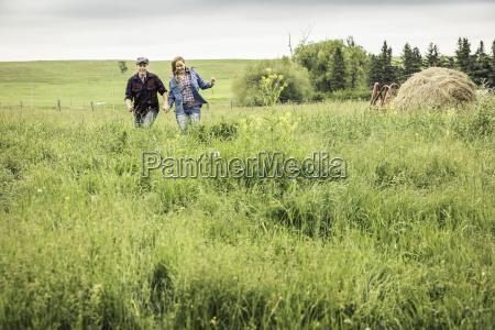 couple holding hands running through field