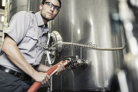 young man in brewery connecting hose