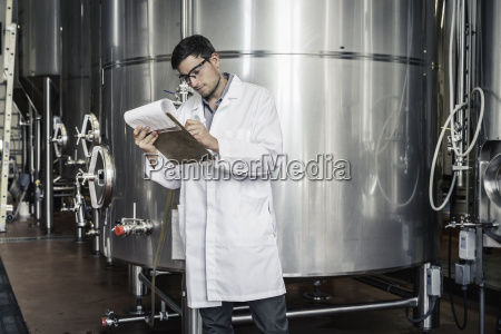 brewer in brewery wearing lab coat