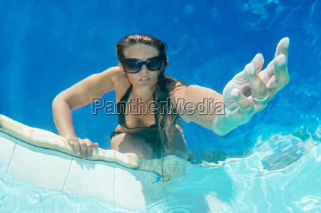 woman holding out hand in pool