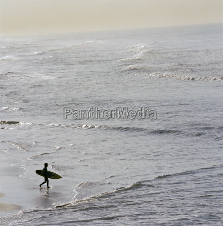 surfer heading into water with board