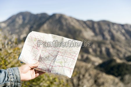 young mans hand holding folding map