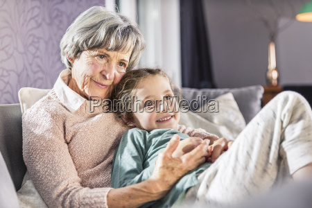 girl on grandmothers lap on sofa