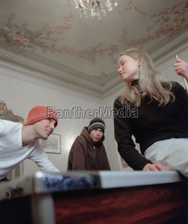 girl and 2 males playing pool