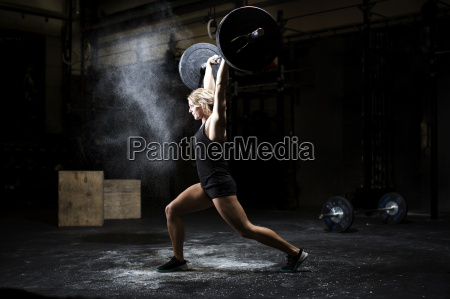 side view of young woman weightlifting