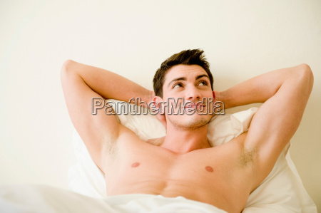 young, man, lying, in, bed - 19475120