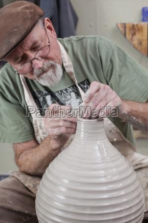 potter wearing flat cap finishing shaping