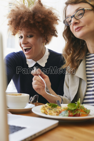 two female friends lunching and looking