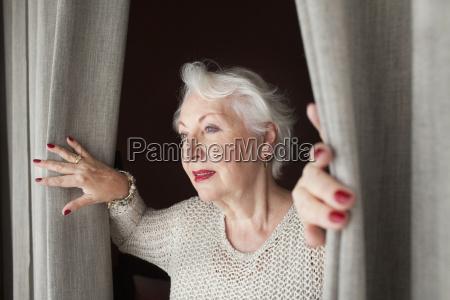 senior woman opening curtains