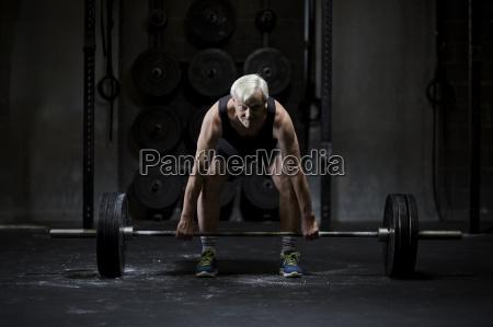 senior man preparing to weightlift barbell