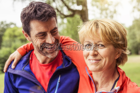 couple wearing sports clothing outdoors smiling