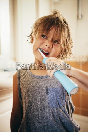 boy using electric toothbrush to brush
