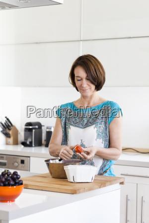 mature woman preparing strawberries in apartment