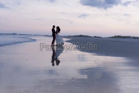couple standing on beach at dusk