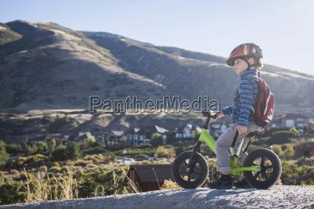 boy sitting on balance bike in