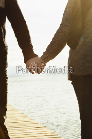 mature couple holding hands mid section