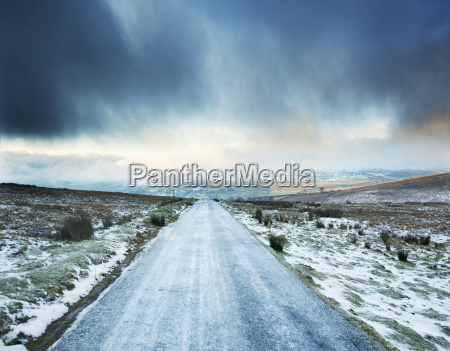 icy rural road with storm clouds