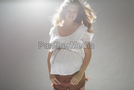 studio portrait of pregnant young woman
