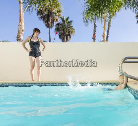 mother watching son splashing in swimming