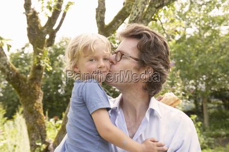 portrait of mature man kissing son