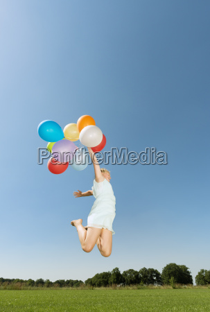 girl holding bunch of balloons jumping